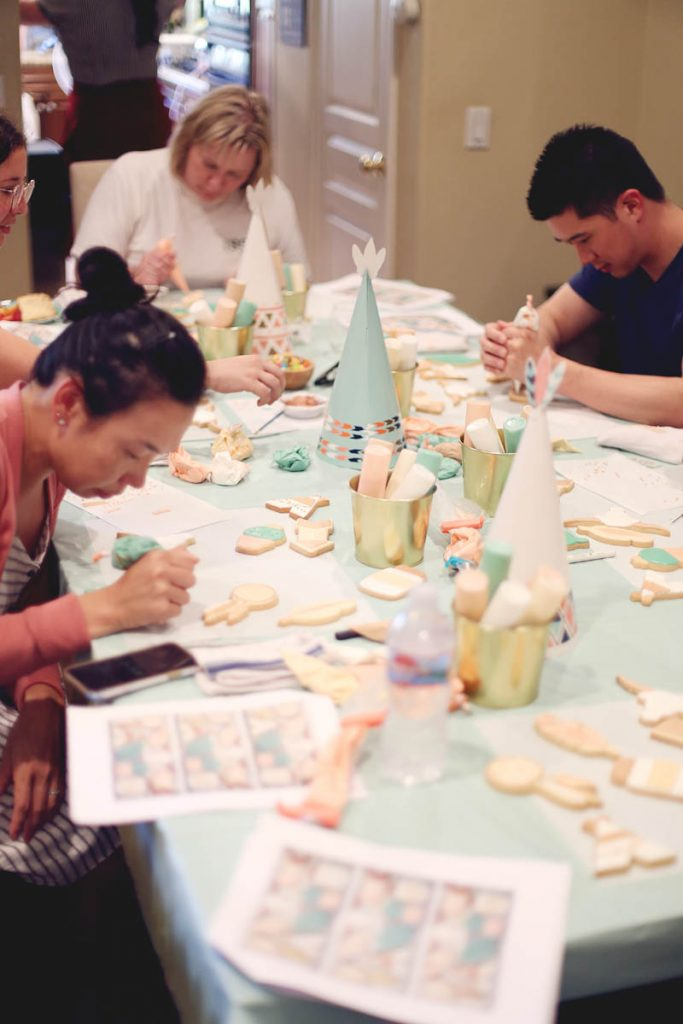 students decorating cookies at a table